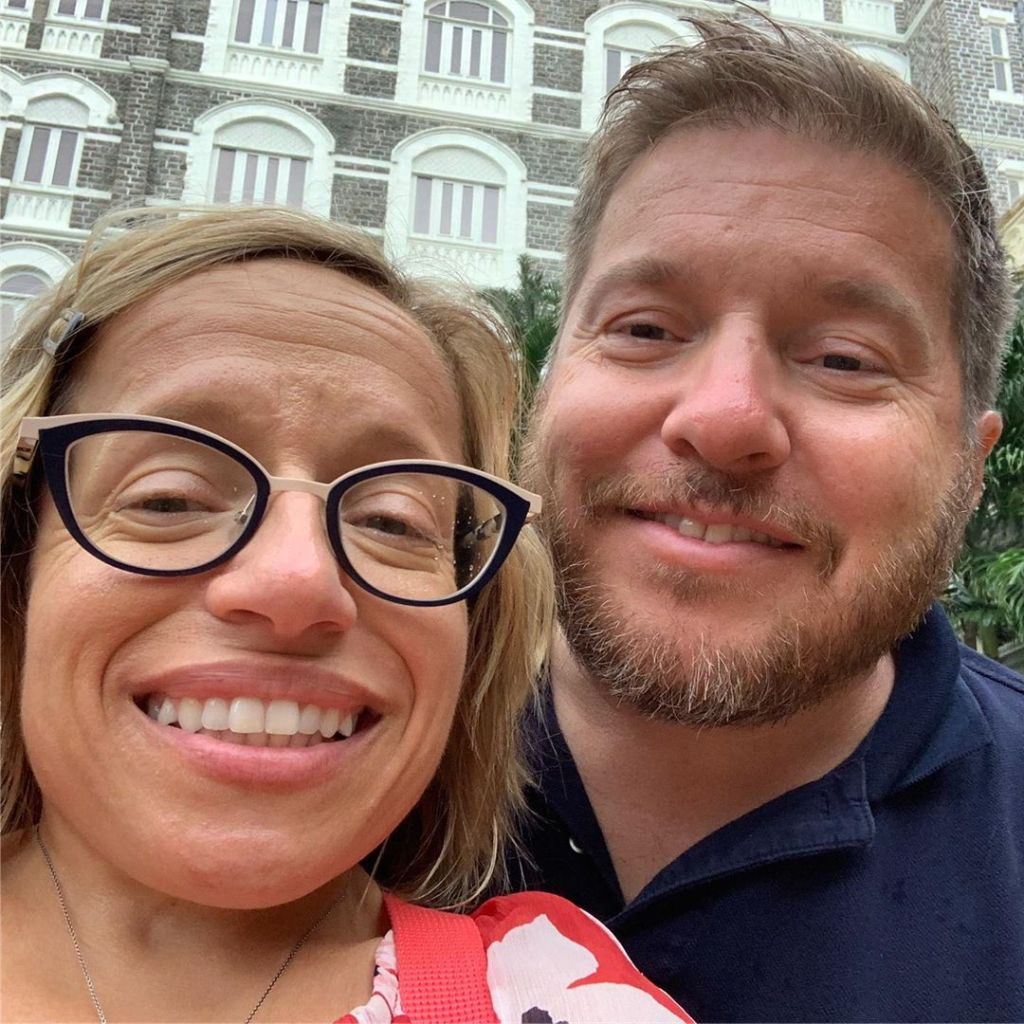 jen arnold and bill klein smiling selfie in front of a brick building