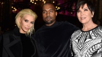 Kim Kardashian with blonde hair sitting with Kanye West and Kris Jenner