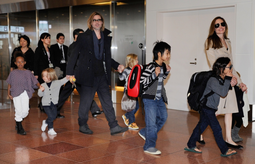 Brad Pitt and Angelina Jolie taking their kids through the airport