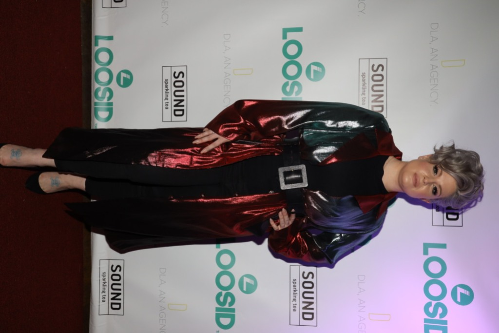 Kelly Osbourne at an event, wearing a long robe and belt