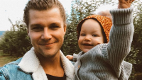 Jeremy Roloff with his baby girl Ember, he is wearing a fleece jean jacket