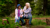 Ami And Billy Brown holding hands on a bench in the woods