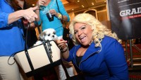 Beth Chapman with a dog wearing a blue shirt at an event