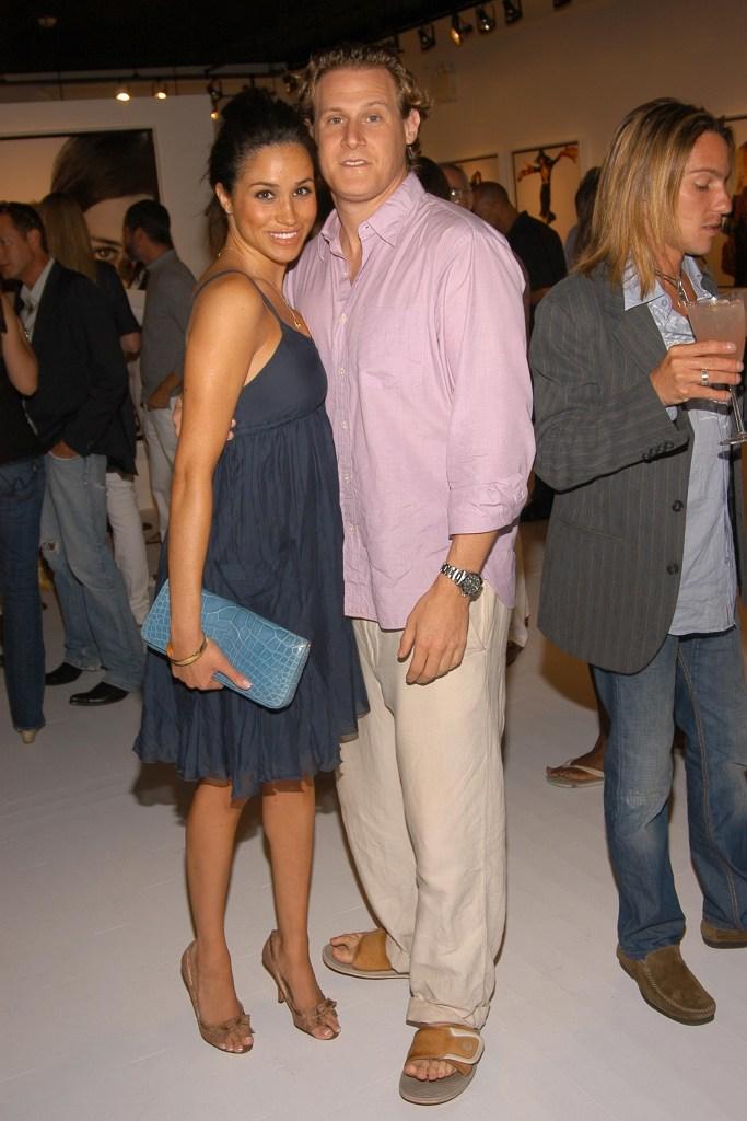 Meghan Markle wearing a gray dress with Trevor Engelson wearing a pink shirt