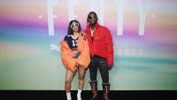 Cardi B in orange coat and Offset in red jacket at an event