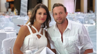 Danielle wearing white with her husband, Adam Busby, also wearing white