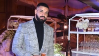 Drake wearing a gray suit drinking some chamapgne