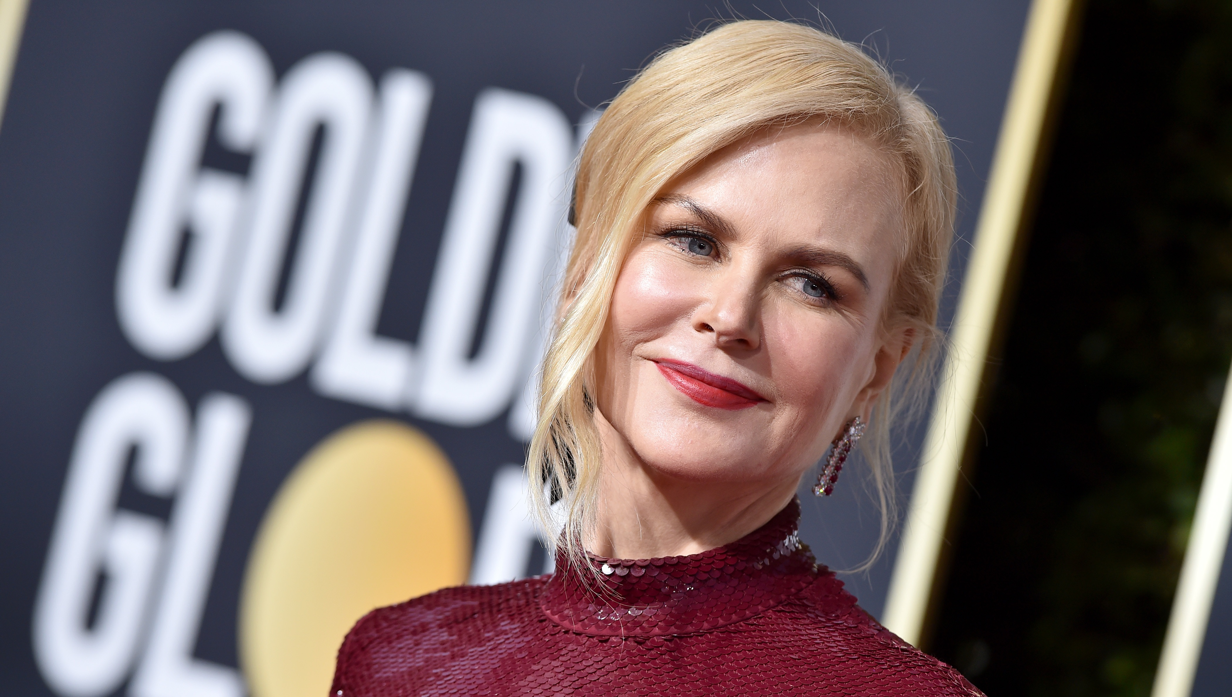 Upclose picture of Nicole Kidman on the Golden Globes red carpet wearing a maroon dress
