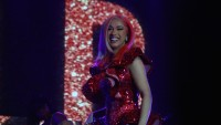 Cardi B wearing a pink outfit and and smiling