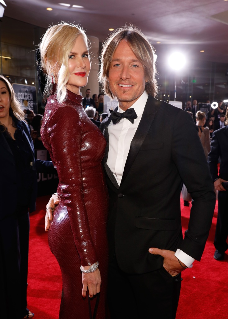 Nicole Kidman wearing maroon with Keith Urban in a suit