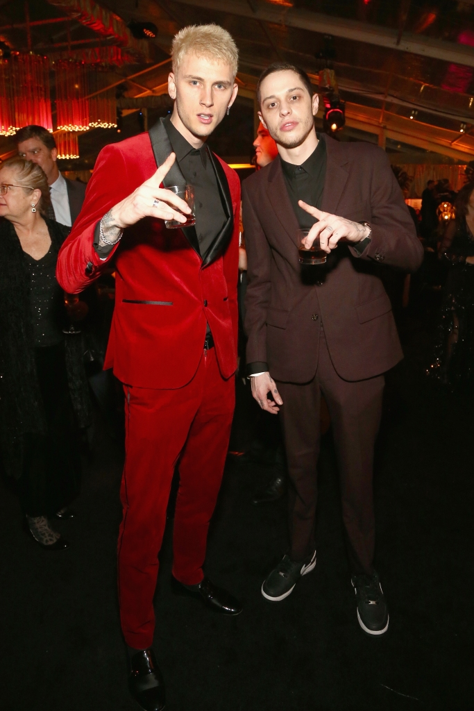 Machine Gun Kelly wearing a red suit with Pete Davidson, also wearing a suit