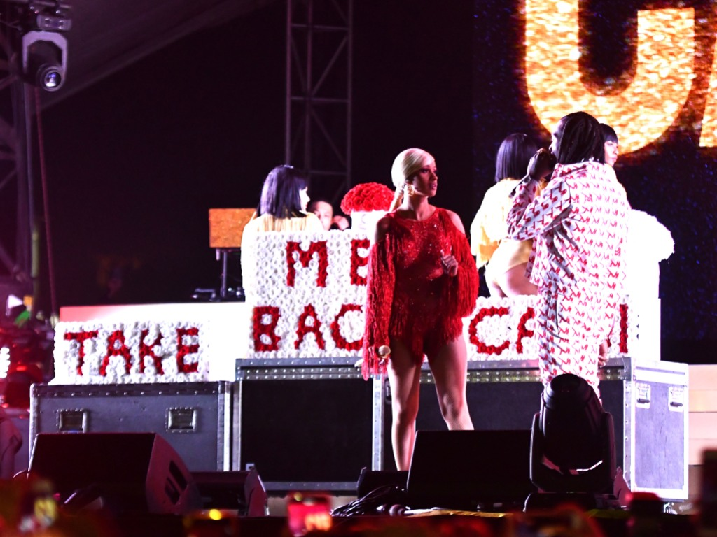 Cardi B wearing a red dress with Offset on stage