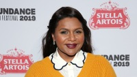 Mindy Kaling wearing a yellow sweater at an event