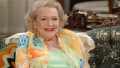 Betty White smiling while sitting on a couch wearing a floral blazer and green top