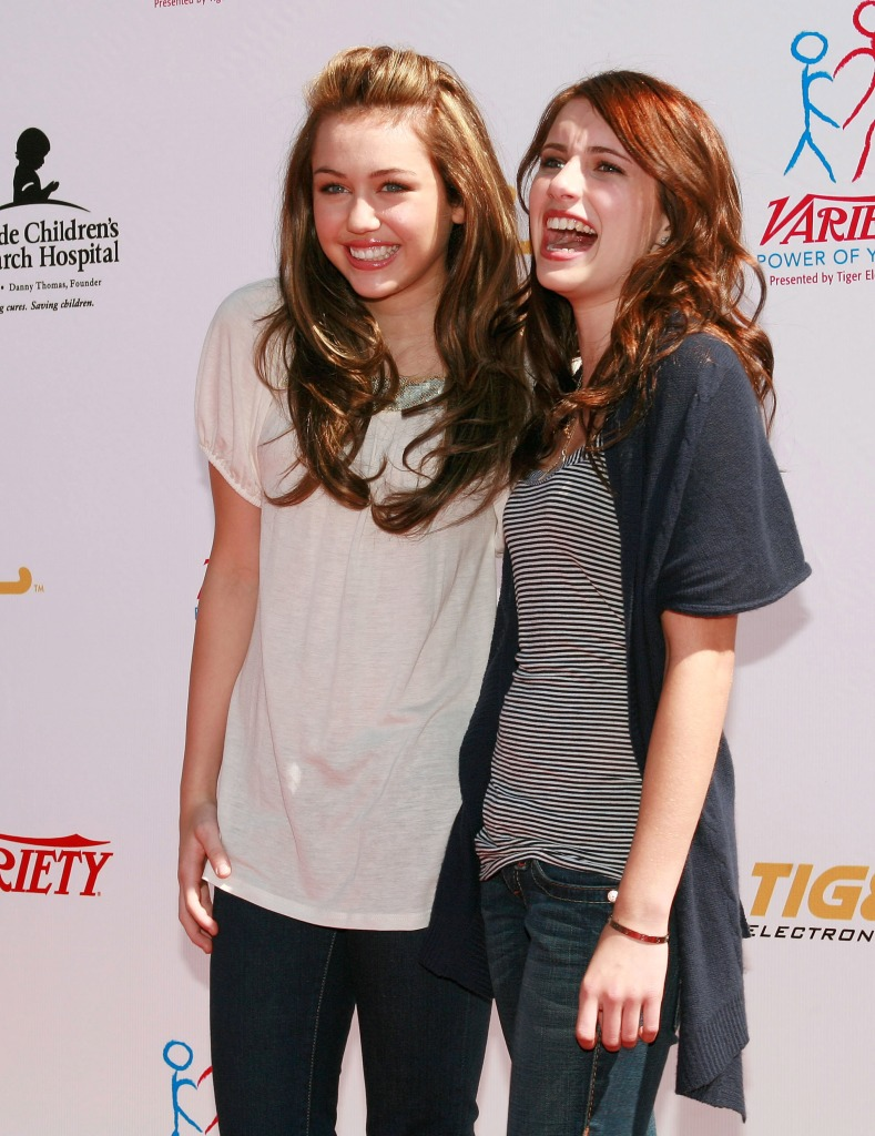 Miley Cyrus wearing a white shirt with Emma Roberts wearing a gray sweater while laughing