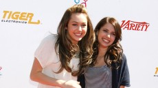 Miley Cyrus wearing a white shirt with Emma Roberts, wearing a striped shirt