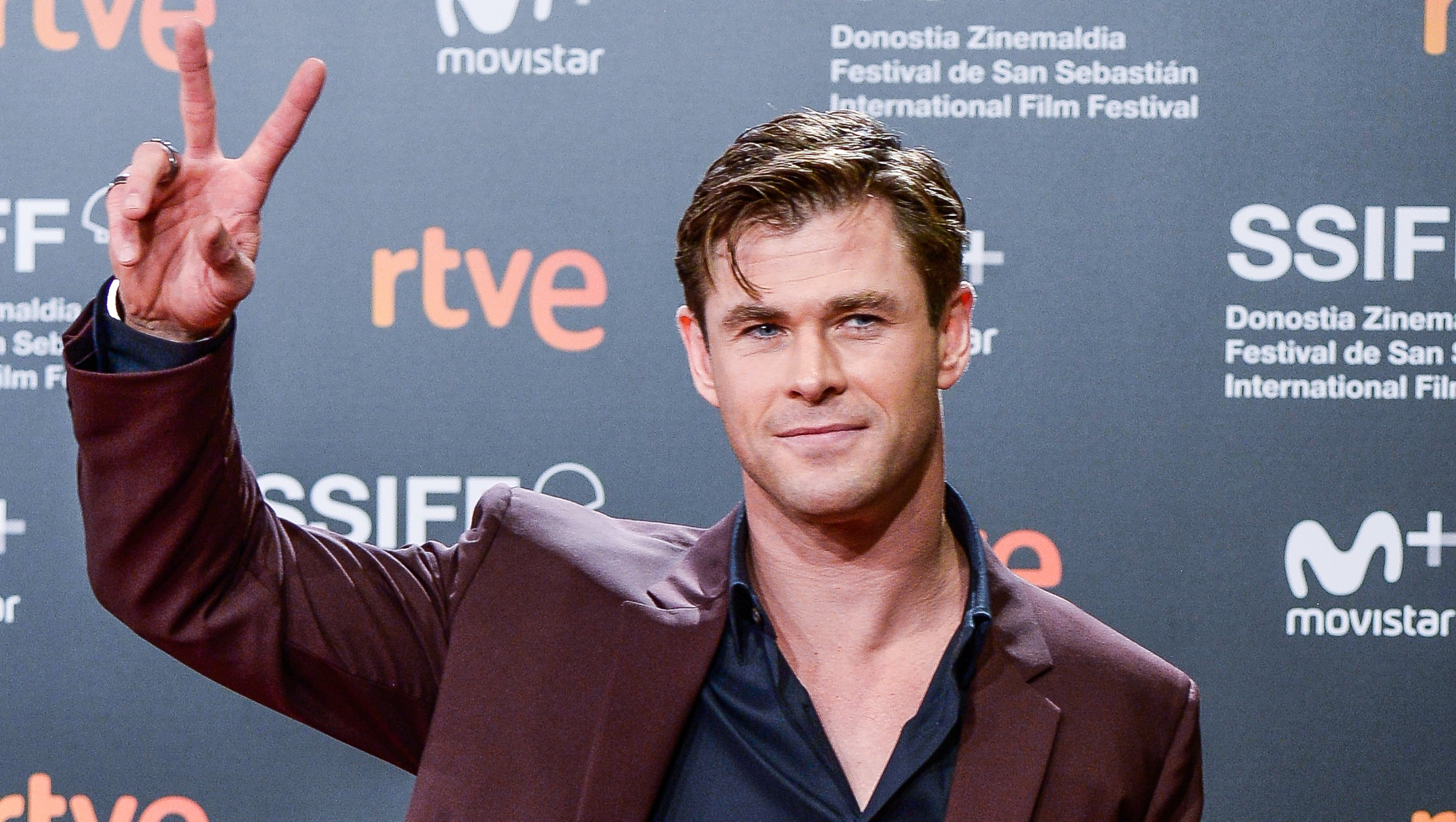 Chris Hemsworth wearing a maroon suit and giving the peace sign