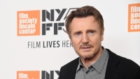 Liam Neeson wearing a black suit at an event