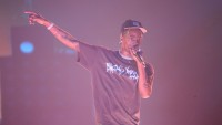 Travis Scott performing on stage in a t-shirt