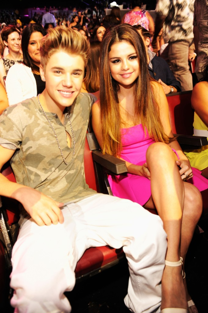 Justin Bieber wearing a camo shirt with Selena Gomez in a pink dress