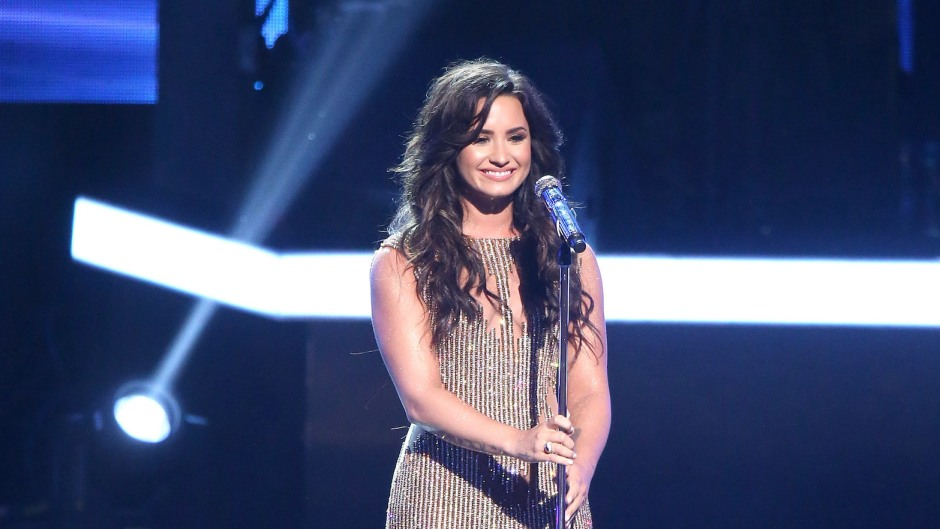 Demi Lovato on stage wearing a sparkly dress