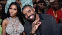 Nicki Minaj wearing a silver outfit with Drake