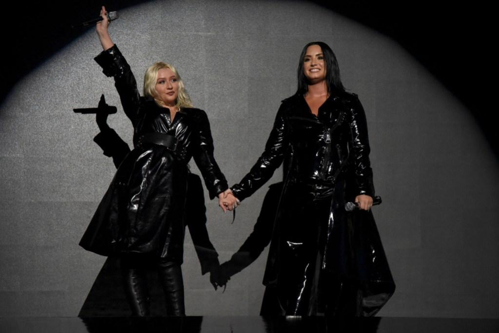 Christina Aguilera wearing all black with Demi Lovato