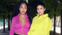Jordyn Woods wearing pink and Kylie Jenner wearing yellow posing together