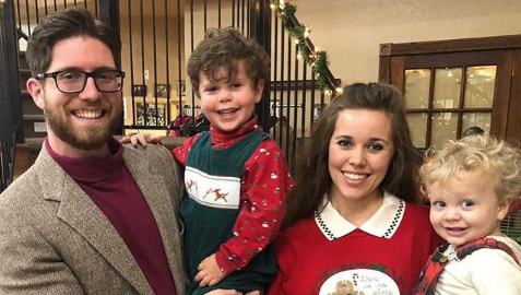 Ben Seewald, Jessa Duggar and their two children posing for a family photo
