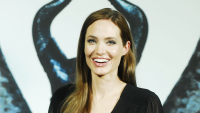 Angelina Jolie with Maleficent horns in the background
