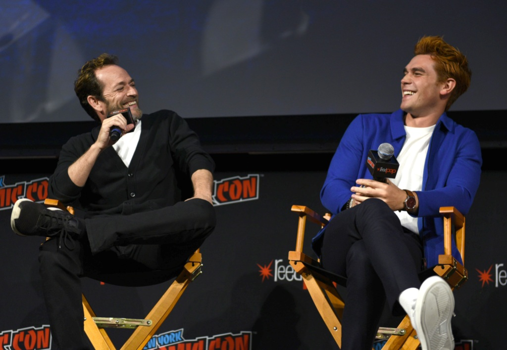 Luke Perry sitting with KJ Apa at an event