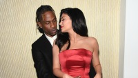 Kylie Jenner wearing a red dress with Travis Scott
