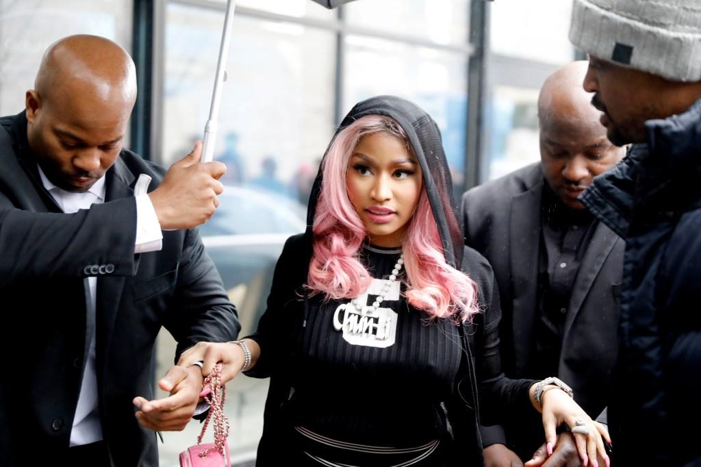 Nicki Minaj has pink hair while wearing a black outfit
