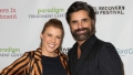 Jodie Sweetin wearing a striped shirt with John Stamos in a black suit