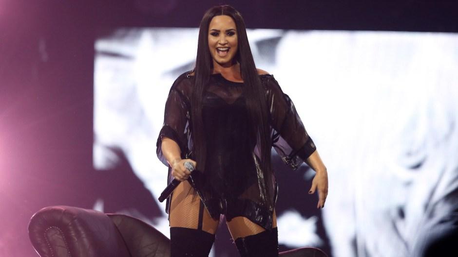 Demi Lovato wearing a black dress onstage
