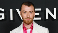 Sam Smith wearing a white suit and pink shirt at Paris Fashion Week.