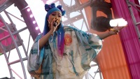 Cardi B Wearing Blue Hair With a Tie Dye Jacket on Stage