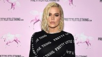 Khloe Kardashian Wearing a Black Shirt in Front of a Pink Background