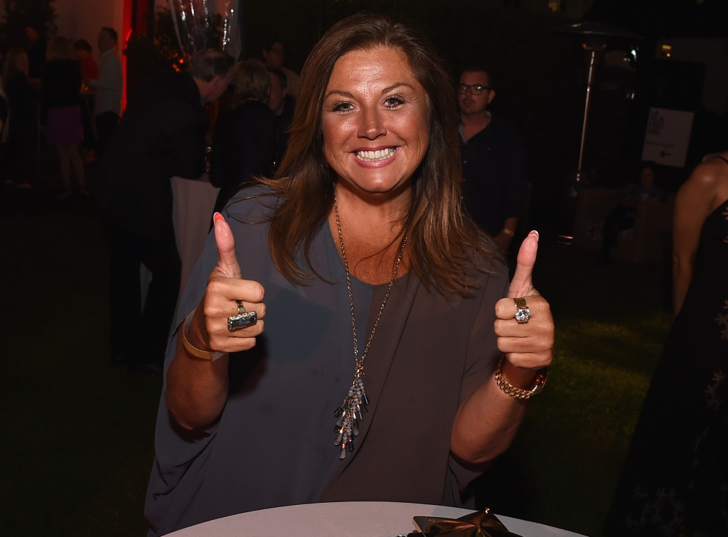 abby lee miller looking happy at an event
