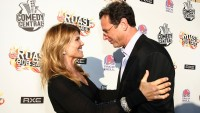 bob saget wearing a suit hugging lori loughlin in a black outfit