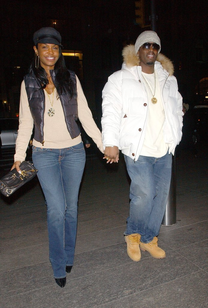 Kim Porter Holding Hands With Diddy Wearing a White Jacket