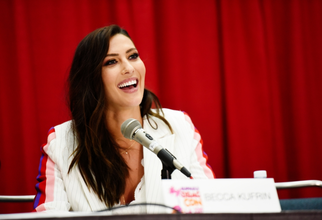 Becca Kufrin Wearing a White Suit on a Panel