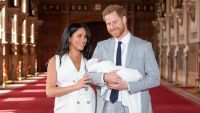 Prince Harry Wearing a Suit With Meghan Markle in White Holding the Baby