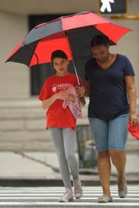 Suri Cruise Wearing a Red Shirt With an Umbrella