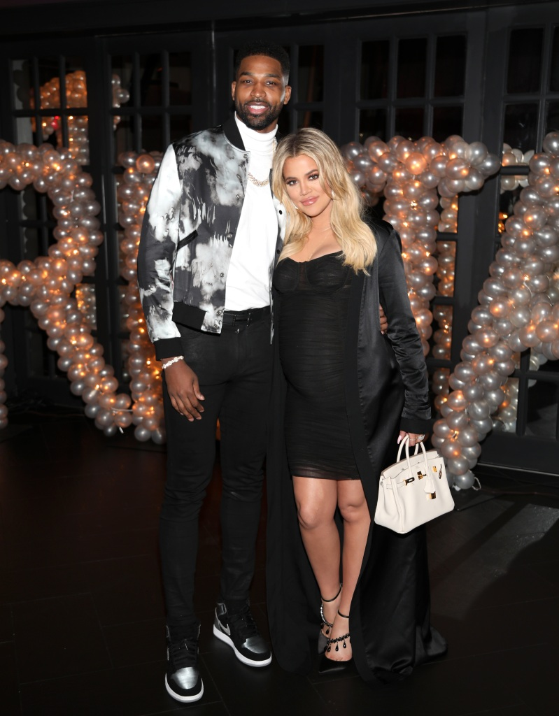Tristan Thompson Wears a Black and White Jacket Standing Arm in Arm With Pregnant Khloe Kardashian in a Black Dress and Black Silk Wrap With a White Handbag