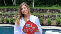 Gia Guidice Holding a Red Graduation Cap With a White Gown on