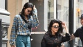 Kourtney Kardashian Wearing a Black Shirt with Sunglasses While Kendall Jenner In Plaid Walks Behind Her