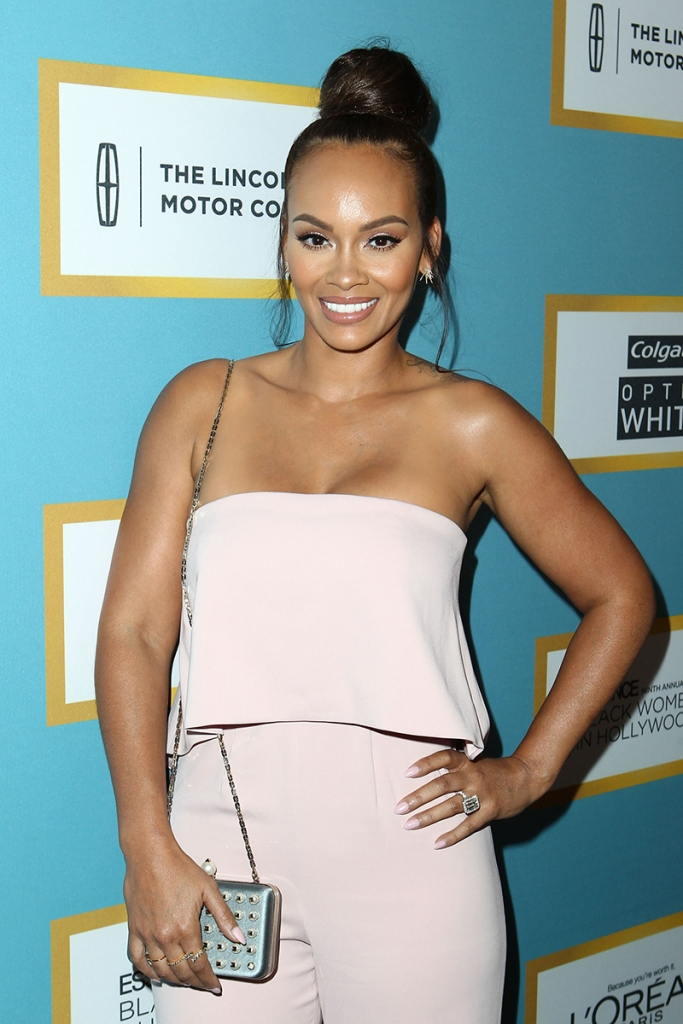 Evelyn Lozada Wearing White Tube Top and Trousers and Hair Bun Smiling and Holding Small Purse