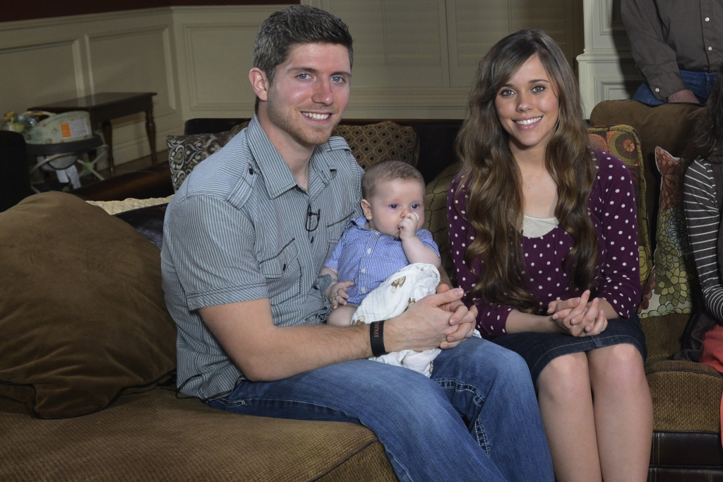 Jessa Duggar wears a purple shirt with lavender polka dots. Ben Seewald wears a grey shirt and jeans while holding their child.