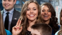 Jessa Duggar gives the peace sign. Shes's wearing a black shirt with beige polka dots.
